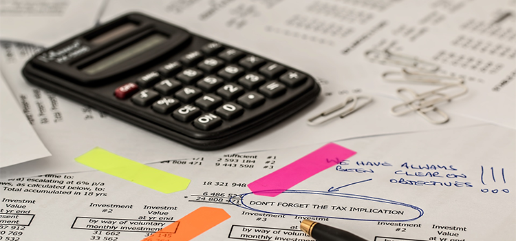 calculator and sticky labels pointing out tax implications on an invoice